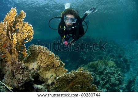 female scuba diver enjoys the buetiful coral - stock photo