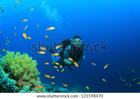 Female Scuba Diver explores coral reef with tropical fish