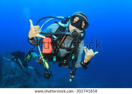 Female scuba diver exploring coral reef underwater with fish - stock photo