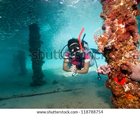 Female SCUBA diver next to a Lionfish underneath a manmade jetty - stock photo