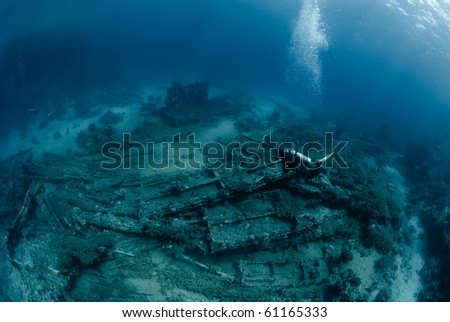 Female scuba diver over Underwater wreckage from the Yolanda, which ran aground during a storm. Yolanda reef, Ras Mohammed national Park Red Sea, Egypt. - stock photo