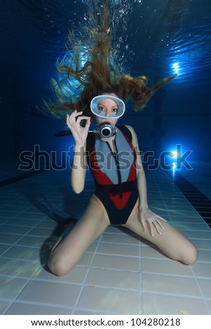 Female scuba diver show hand signal - stock photo