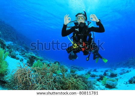 Female Scuba Diver swimming over a coral reef signals that she is Okay - stock photo