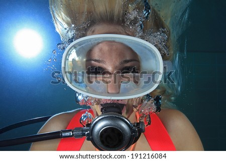Female scuba diver underwater with water inside mask  - stock photo