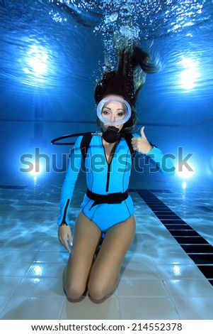 Female scuba diver with lycra suit show hand signal underwater in the pool  - stock photo