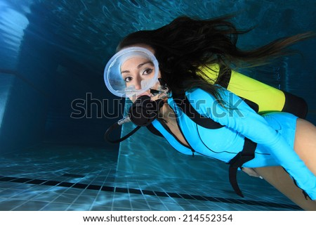 Female scuba diver with lycra suit underwater in the pool  - stock photo