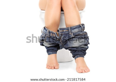 Female seated at a toilet with her pants down isolated on white background - stock photo