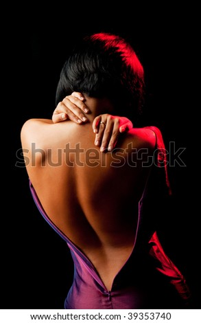 female seen from the back, undressing and holding her neck - stock photo
