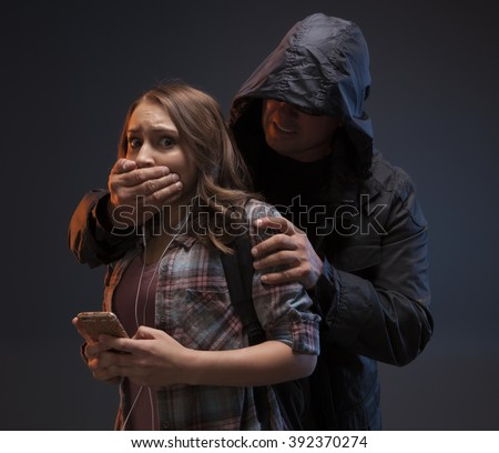 FEMALE SELF DEFENSE SERIES- Scary man grabs a girl on her phone.  Teenage Girl gets attacked by a stranger while she's on her phone. - stock photo