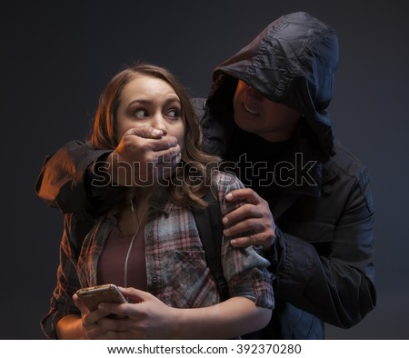 FEMALE SELF DEFENSE SERIES- Teenage Girl on a cell phone gets attacked by a stranger. He has his hand on her mouth and she's afraid. - stock photo