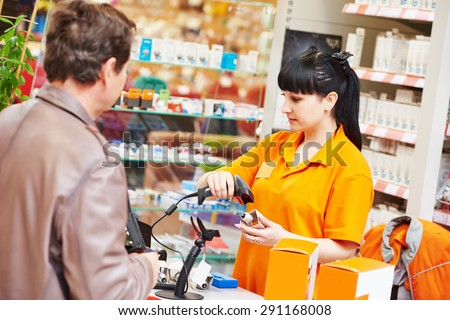 female seller cashier using barcode scanner during selling lamp to purchaser in hardware shopping mall supermarket - stock photo