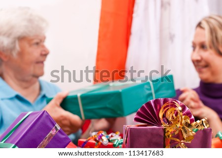 female senior and young women give presents to each other