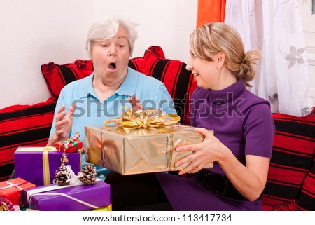 female senior gets a present from a pretty young