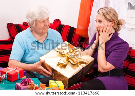 female senior gives present to young blonde woman