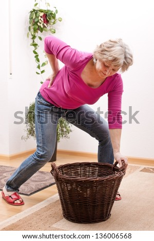 female Senior has back pain due to heavy load - stock photo