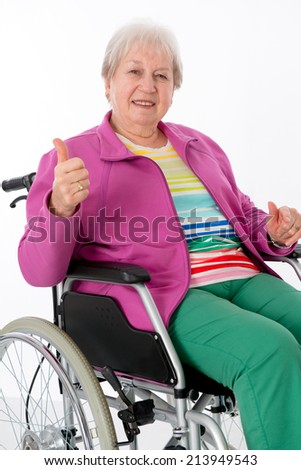 female senior in wheelchair with thumb up