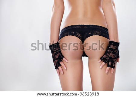 Female sexy back with hand in a black glovers is on her buttocks - stock photo