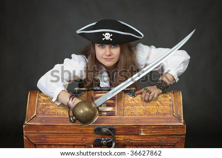 Female sexy pirate with chest of treasure and saber on black background.