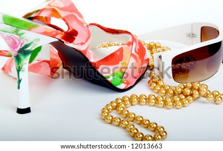 Female shoe, pearls and sunglasses - stock photo