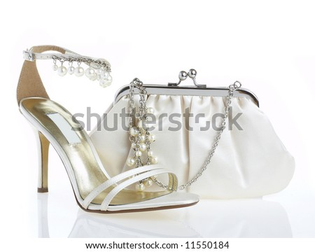 Female shoes and handbag on it is white a background - stock photo