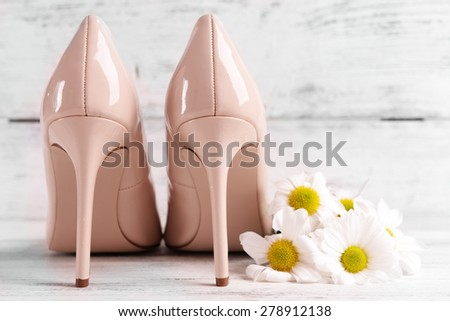 Female shoes with flowers on wooden background - stock photo