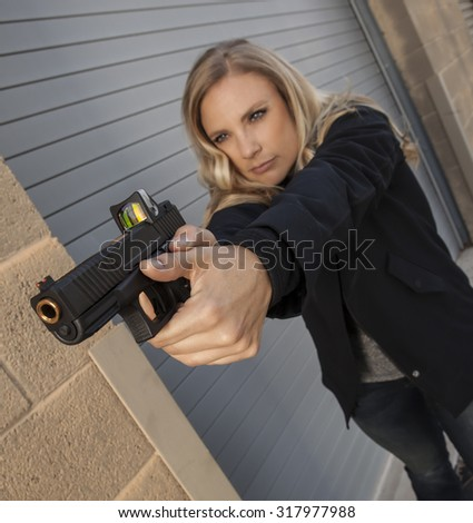 Female shooter aiming gun outdoors. | REFUSE TO BE A VICTIM Collection - stock photo