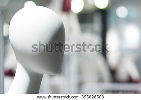 Female shop dummy fashion mannequin in department store boutique window wearing current fashions in clothes. - stock photo