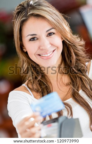 Female shopper paying by credit card at a store - stock photo