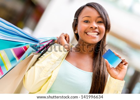 Female shopper with a credit card looking very happy - stock photo