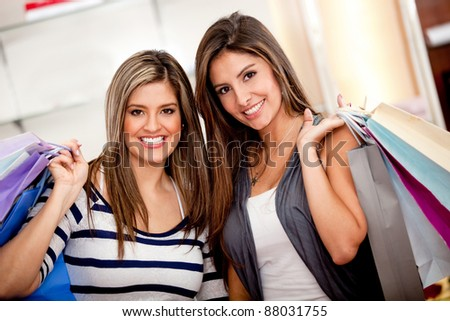 Female shoppers at a store with bags and smiling