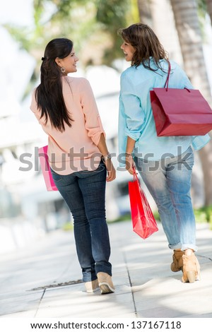 Female shoppers at the mall in Miami holding shopping bags - stock photo