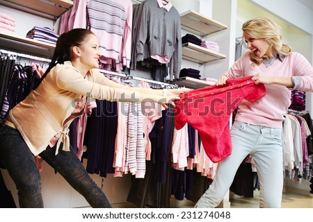 Female shoppers fighting for the last tanktop in department store - stock photo