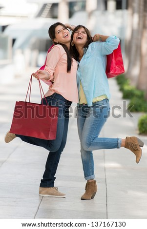 Female shoppers having fun shopping looking very happy - stock photo