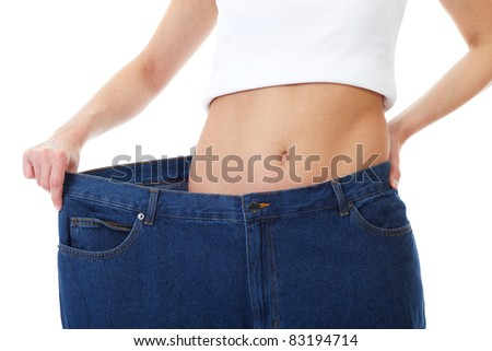 female shows her old huge pair of jeans, weight loss concept, studio shoot - stock photo