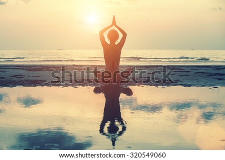 Female silhouette in yoga with reflection in water, meditation pose at amazing sunset. - stock photo