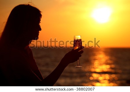 Female silhouette on sea sunset with  glass in hand - stock photo