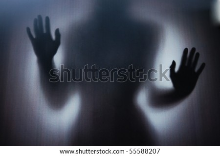 Female Silhouette photographed through a dark glass