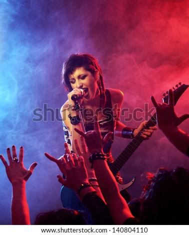 Female singer and guitarist playing guitar at a rock concert - stock photo