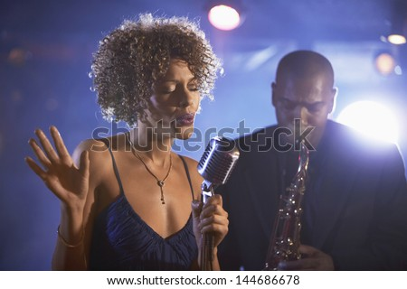 Female singer and saxophonist performing at the jazz club - stock photo