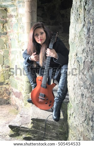Female singer dressed in black with guitar taken in vertical format