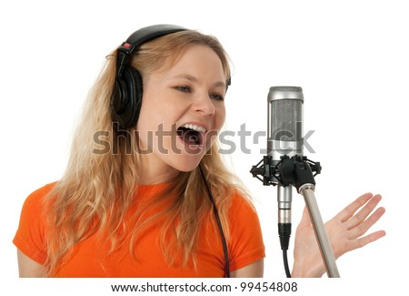 Female singer in headphones singing with the microphone. Isolated on white background. - stock photo