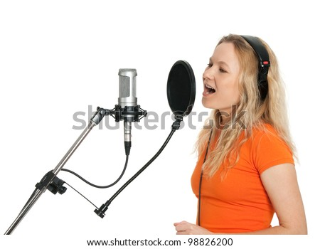 Female singer in orange t-shirt singing with studio microphone. Isolated on white background. - stock photo