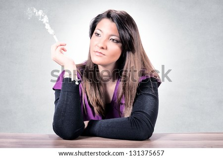 Female siting on the table and smoking cigarette