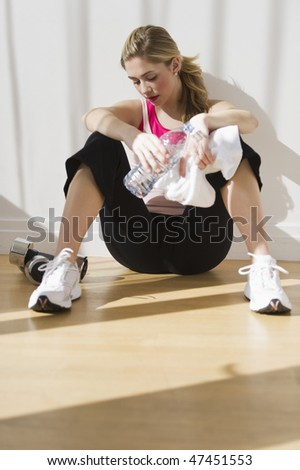 female sitting alone against wall after workout with water and towel - stock photo