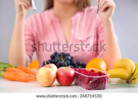 Female sitting at desk front lot of fruits, healthy food - stock photo