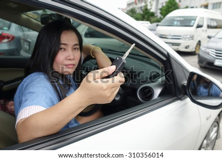 Female sitting in car showing key at the car parking