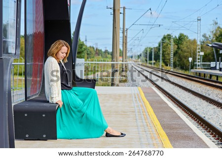 Female sitting on the bench waiting train on the platform of railway station - stock photo