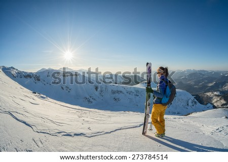 female skier looking at the sunset from the top of the mountain. fisheye shot