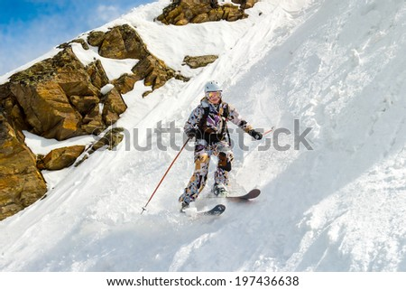 Female skier on a very steep off-piste in the background of rocks. In sunny weather. - stock photo