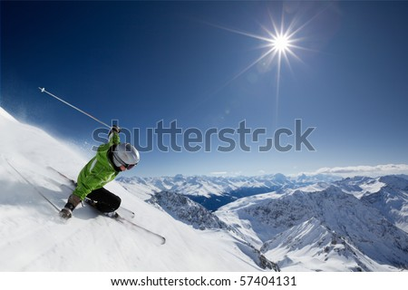 Female skier on downhill race with sun and mountain view. - stock photo